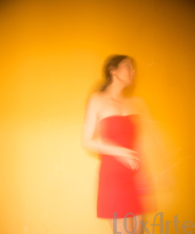 Carefree young woman in red dress dancing in front of a hot yellow background.