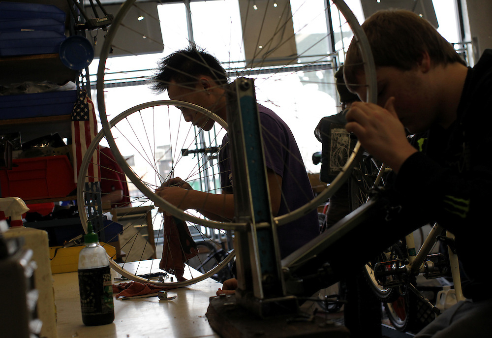 Youth Express apprentices Koua Yang, 15, left, and Marcus Wachholz, 17, work to straighten wheels on donated bikes at Express Bike Shop in St. Paul, Minnesota.  By refurbishing and selling bicycles, youth apprentices learn mechanical, business, and entrepreneurial skills..