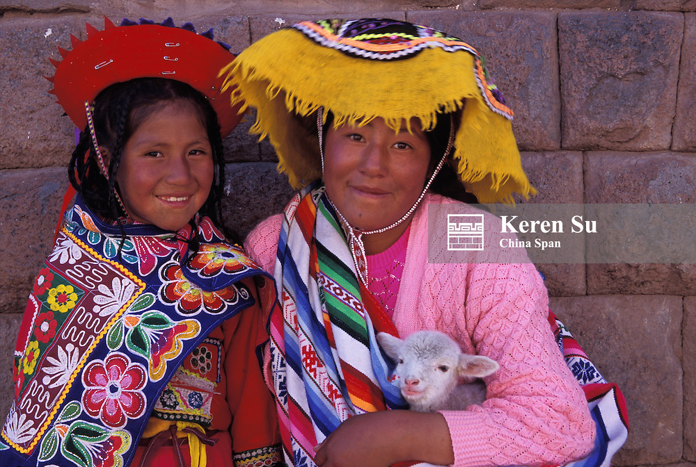 Two Indian girls holding a lamb in front of ancient Inca stone wall, Cuzco, Peru