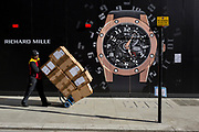 A courier delivers boxes and walks past a construction hoarding of a watch outside the new Richard Mille shop in New Bond Street, on 25th February 2019, in London, England.