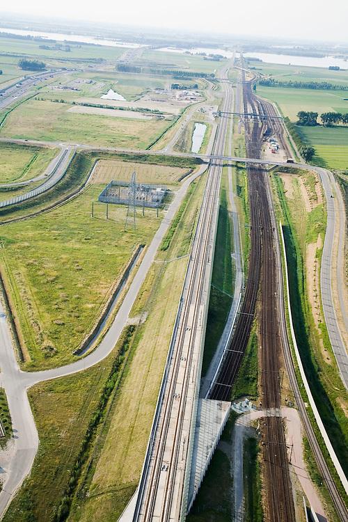 Nederland, Noord-Brabant, Zevenbergschen Hoek, 04-07-2006; spoorkruising: uiterst links de gloednieuwe HSL, komend vanuit Breda; geheerechts de reguliere spoorlijn (ook vanuit de richting Breda); de spoorlijn vanuit Roosendaagaat onder de HSdoor (de betreffende fly-over, onder in beeld)) en voegt zich tussen bij (en tussen) beide andere spoorlijnen; in de verte het Hollandsch Diep; in het midden, links van de sporen, een elektriciteits-station wat de HSvan stroom voorziet; energie, spanning, voeding, spoorviaduct, beton, bouw, constructie, transport, infrastructuur, verkeer en vervoer, mobiliteit, hogesnelheidslijn, spoor, rail, HSL, TGV, planologie, ruimtelijke ordening, landschap;;zie ook andere foto's van deze lokatie (lucht en panorama); deevan de serie Panorama Nederland; luchtfoto (toeslag); aerial photo (additional fee required); .foto Siebe Swart / photo Siebe Swart
