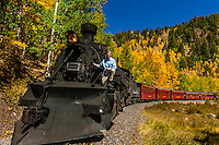 Governor John Hickenlooper (of Colorado)  on a visit aboard the the Cumbres & Toltec Scenic Railroad, from Antonito to Osier, Colorado during peak autumn color. The Cumbres & Toltec Scenic Railroad has been jointly owned by the States of Colorado and New Mexico since 1970 when it was purchased from the Denver and Rio Grande Western Railway, which was going to scrap the line. The train makes a 64 mile run between Antonito, Colorado and Chama, New Mexico. The railroad is the highest and longest narrow gauge steam railroad in the United States with a track length of 64 miles. The train traverses the border between Colorado and New Mexico, crossing back and forth between the two states 11 times. The narrow gauge track is 3 feet wide. It runs over 10,015 ft (3,053 m) Cumbres Pass.