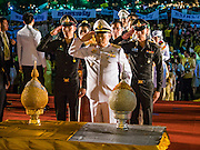 05 DECEMBER 2015 - BANGKOK, THAILAND:  Thai police officers salute after they presented the King's representatives with gifts that represent lotus buds on the King's Birthday on Sanam Luang in Bangkok. Thais marked the 88th birthday of Bhumibol Adulyadej, the King of Thailand,  Saturday. The King was born on December 5, 1927, in Cambridge, Massachusetts. The family was in the United States because his father, Prince Mahidol, was studying Public Health at Harvard University. He has reigned since 1946 and is the world's currently the longest serving monarch in the world and the longest serving monarch in Thai history. Bhumibol, who is in poor health, is revered by the Thai people. His birthday is a national holiday and is also celebrated as Father's Day. He is currently hospitalized in Siriraj Hospital, recovering from a series of health setbacks.   PHOTO BY JACK KURTZ