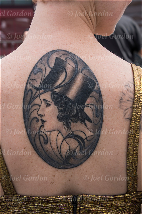 Tattoo of 1920's woman's wearing top hat in profile on her back.<br /> <br /> Tattoos are no longer just a male thing, young women are just as likely to get a tattoo as males. <br /> <br /> Body art or tattoos has entered the mainstream it is no longer considered a weird kind of subculture.<br /> <br /> &quot;According to a 2006 Pew survey, 40% of Americans between the ages of 26 and 40 have been tattooed&quot;.