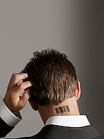 Young man with bar code tattoo on his neck scratching head back view