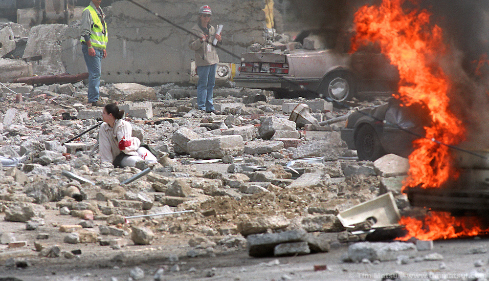 A one-armed victim kneels in the rubble as controllers watch during a mock terrorist attack south of downtown on Monday, May 12, 2003 in Seattle, Washington. Controllers set off an explosion shortly after noon which simulated the detonation of a radioactive dispersal device or 'dirty bomb.'
