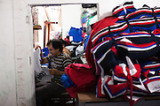Rosmery's husband sewing in their home where they live with their seven children and her grandson.<br /> <br /> Rosmery and her husband are Bolivian and moved to Brazil in search of work. Prior to moving in to their own home they lived and worked in a sewing workshop with their family, often for up to 16 hours a day. <br /> <br /> Nowadays they still sews and have long days, but they are based from home.<br /> <br /> They have received a lot of help and support from Missao Paz who work in partnership with C&A Foundation to  offer advice and support on employment, health, family, community and education.