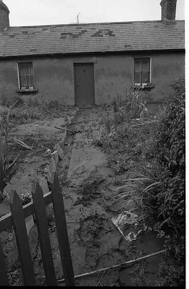 "Flooding at the Dodder..1986..26.08.1986..08.26.1986..28th August 1986..As a result of Hurricane Charly (Charlie) heavy overnight rainfall was the cause of severe flooding in the Donnybrook/Ballsbridge areas of Dublin. In a period of just 12 hours it was stated that 8 inches of rain had fallen. The Dodder,long regarded as a ""Flashy"" river, burst its banks and caused great hardship to families in the 300 or so homes which were flooded. Council workers and the Fire Brigades did their best to try and alleviate some of the problems by removing debris and pumping out some of the homes affected..Note: ""Flashy"" is a term given to a river which is prone to flooding as a result of heavy or sustained rainfall...After some of the flooding had receded sild and mud deposits were pictured right up to the door of the cottage."