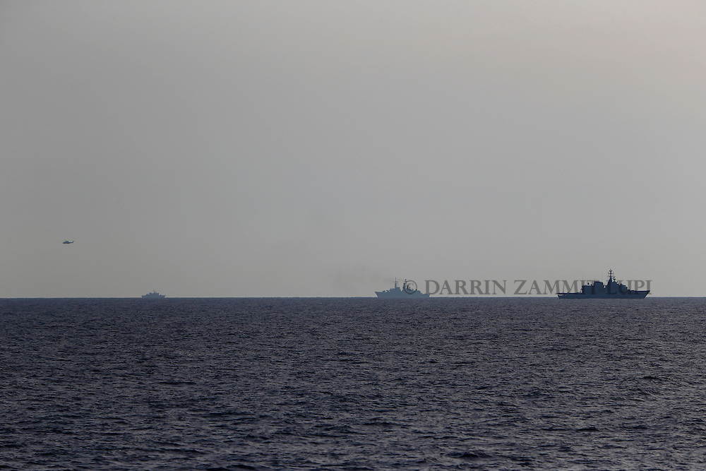Naval and coast guard vessels and a helicopter search for missing migrants after their boat capsized off the coast of Libya August 5, 2015.  A boat packed with up to 700 African migrants capsized in the Mediterranean Sea off the coast of Libya on Wednesday and many were feared dead, officials and aid agencies said. <br /> REUTERS/Darrin Zammit Lupi <br /> MALTA OUT. NO COMMERCIAL OR EDITORIAL SALES IN MALTA