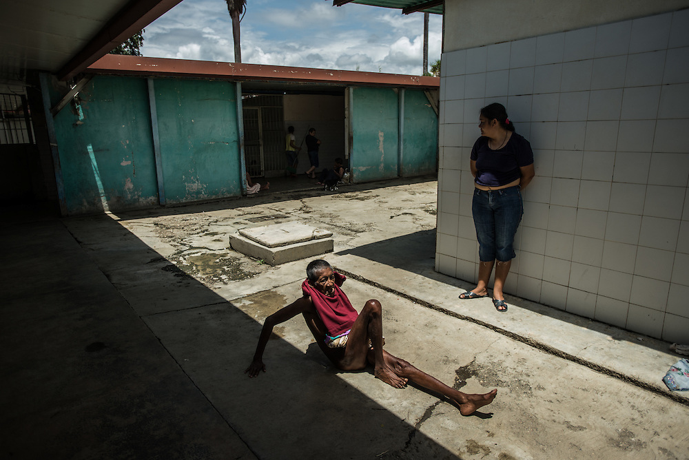 BARQUISIMETO, VENEZUELA - AUGUST 25, 2016: Schizophrenic patient, <br /> Alegr&iacute;a Flores, 72, crawls on the floor with her clothes put on wrong. She constantly takes off her clothes and puts each item around her neck like scarves. She does not have all of the medicines that she needs to control her disorder, and regularly urinates and defecates on herself. Her skin is infected with scabies. The economic crisis that has left Venezuela with little hard currency has also severely affected its public health system, crippling hospitals like El Pampero Psychiatric Hospital by leaving it without the resources it needs to take care of patients living there, the majority of whom, like Alegr&iacute;a, have been abandoned by their families and rely completely on the state to meet their basic needs. The hospital does not even have basic hygiene or cleaning supplies.  There is no soap, no shampoo, no tooth paste, no toilet paper.  Patients relieve themselves in the common areas and patio area, and clean themselves only with water. Nearly every patient is infected with scabies because they do not have the resources to bathe properly or to have their threadbare, misfitted clothes washed as often as needed. To make matters worse, the hospital only has running water a few hours a day.  PHOTO: Meridith Kohut
