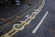 Double-yellow lines painted over lettering stating a clearway to a local business.