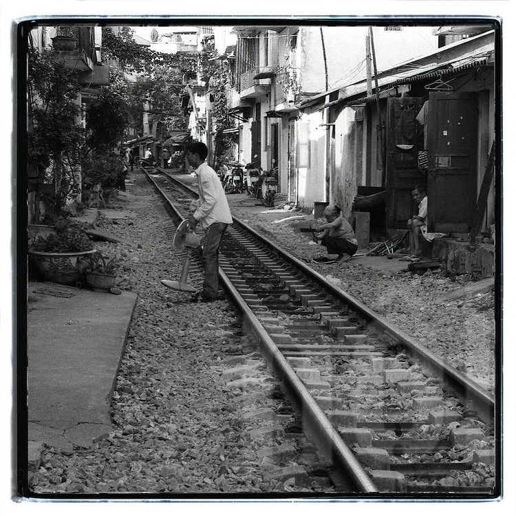A man carries a fan and cross the railway. This railway go through buildings and houses. People live with the train crossing in front of their door.