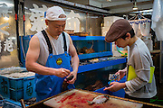 While preparing the fish, a fishmonger talks to a curious youngster.