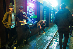 """© Licensed to London News Pictures . 23/12/2017. Manchester, UK. A man sits in the window of a takeaway on Bootle Street , leaning over a pool of vomit between his feet . Revellers out in Manchester City Centre overnight during """" Mad Friday """" , named for being one of the busiest nights of the year for the emergency services in the UK . Photo credit: Joel Goodman/LNP"""