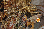 Detail of angel with trumpet, putto and crown, from the gilded sculptural motif of crown and angels exalting the King and Portugal, above the portrait of King John V or Joao V, in the Black Room of the Joanina Library, or Biblioteca Joanina, a Baroque library built 1717-28 by Gaspar Ferreira, part of the University of Coimbra General Library, in Coimbra, Portugal. The Casa da Livraria was built during the reign of King John V or Joao V, and consists of the Green Room, Red Room and Black Room, with 250,000 books dating from the 16th - 18th centuries. The library is part of the Faculty of Law and the University is housed in the buildings of the Royal Palace of Coimbra. The building is classified as a national monument and UNESCO World Heritage Site. Picture by Manuel Cohen