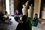 Pramila  Tharu (right), 15, is interviewed by The Guardian reporter Zoe Williams as she cradles her 2 year old toddler Prapti, in Bhaishahi village, Bardia, Western Nepal, on 29th June 2012. Pramila eloped and married at 12 and gave birth to Prapti at age 13. She delivered prematurely on the way to the hospital in an ox cart and her baby weighed only 1.5kg at birth. In Bardia, StC works with the district health office to build the capacity of female community health workers who are on the frontline of health service provision like ante-natal and post-natal care, especially in rural areas. Photo by Suzanne Lee for Save The Children UK