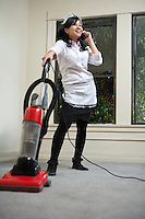 Full length young housemaid using cell phone while vacuuming