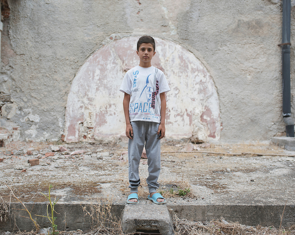 Diar, a 13 year old Syrian Kurd, stands in the ruins of the abandoned Lepida psychiatric hospital. <br />