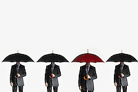 Businessmen holding umbrellas standing side by side one red umbrella