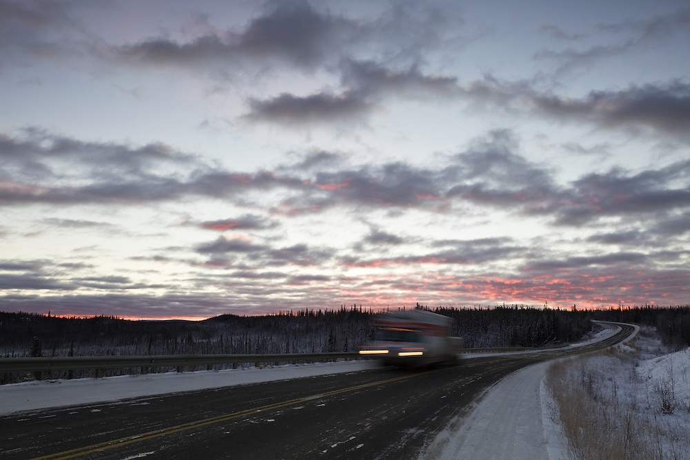 An early winter sunrise creates a pink alpenglow in the sky near the Tetlin National Wildlife Refuge as a vehicle passes by on the Alaska Highway in interior Alaska. Morning.