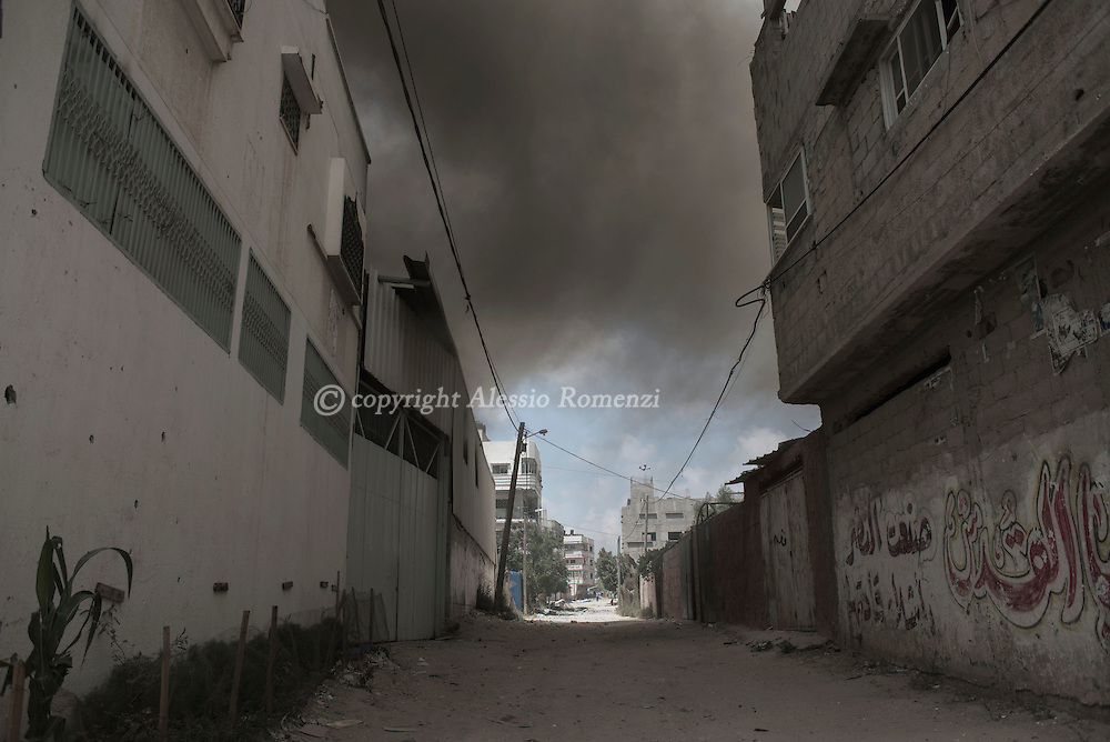 Gaza Strip, Gaza City: Following a heavy Israeli attack by shelling and airstrike, smoke is seen in Shujaya district during a humanitarian ceasefire admitted in Gaza proposed by the International Committee of the Red Cross by two hour. ALESSIO ROMENZI