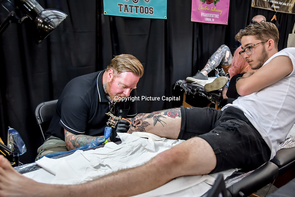 Richardson Tattoos, Tattoo a client at The Great British Tattoo Show, on 26 May 2019, London, UK.