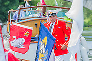 The Royal Swan Uppers, who wear the scarlet uniform of Her Majesty The Queen, travel in traditional rowing skiffs together with Swan Uppers from the Vintners' and Dyers' livery companies. They are led by David Barber(pictured), the Queen's Swan Marker. Swan Upping plays an important role in the conservation of the mute swan and involves The Queen's Swan Warden collecting data, assessing the health of young cygnets and examining them for any injuries. Cygnets are extremely vulnerable at this early stage in their development and Swan Upping affords an opportunity to help both adults and cygnets that might otherwise go untreated. The River Thames, London, UK.