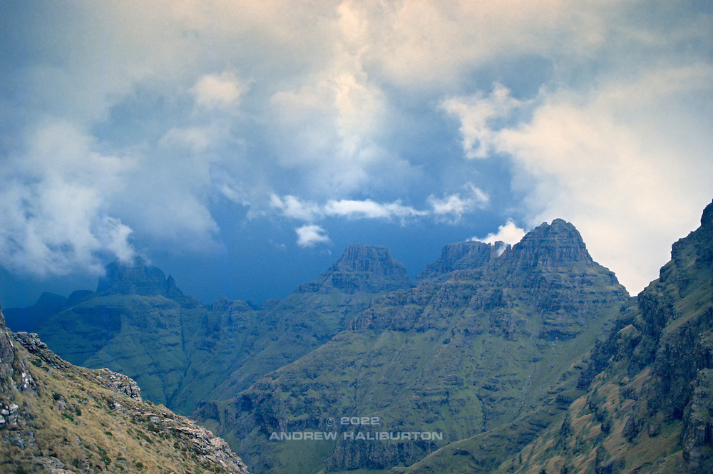 Storm engulfs the Cathedral Ridge, viewed from Ntonjelana Pass in the uMlambonja Wilderness area of the Drakensberg.  The major peaks of the ridge are from left to right: Cathedral Peak 3004m, Outer Horn 3005m, Inner Horn 3005m and Mitre 3023m.  The Bell 2930m is barely visible  because it is superimposed on Cathedral Peak (left).  uKhahlamba-Drakensberg Park, KwaZulu-Natal, South Africa.  Chinon CM5, 28/2.8. Fuji RD. November 1988.