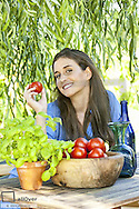 Young, beautiful woman in garden, tomatoes, herbs and water bottles in garden (model-released)