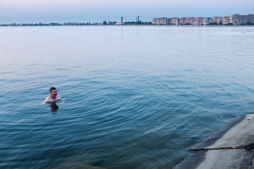 A man swimming in Morii Lake which he does each afternoon after he finishes his job. 'The water is clear, the temperature is perfect. This is how i get rid of my black thoughts', he says. The lake was built in the communist-era covering a residential area which included a cemetery and a Church.