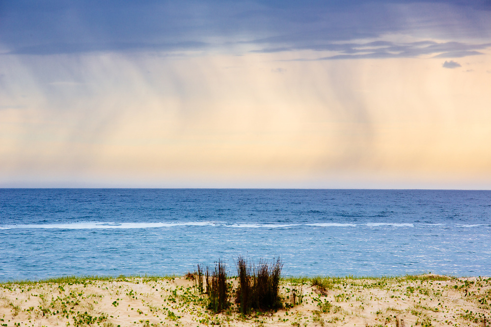 Rain falling above the ocean creating a windswept pattern in the sky above Depot Beach. Murramarang National Park.