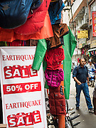 """06 AUGUST 2015 - KATHMANDU, NEPAL: A sign announcing an """"Earthquake Sale"""" at a store that sells hiking and trekking supplies to tourists in Kathmandu. Tourism, which accounts for about 8% of the Nepal economy, has virtually collapsed since the earthquake in April causing more damage to the Nepali economy. The areas most heavily damaged, historic sites in the Kathmandu valley and trekking trails in the Himalaya Mountains, are the most popular tourist areas and the earthquake struck in the middle of the tourist high season. The Nepal Earthquake on April 25, 2015, (also known as the Gorkha earthquake) killed more than 9,000 people and injured more than 23,000. It had a magnitude of 7.8. The epicenter was east of the district of Lamjung, and its hypocenter was at a depth of approximately 15km (9.3mi). It was the worst natural disaster to strike Nepal since the 1934 Nepal–Bihar earthquake. The earthquake triggered an avalanche on Mount Everest, killing at least 19. The earthquake also set off an avalanche in the Langtang valley, where 250 people were reported missing. Hundreds of thousands of people were made homeless with entire villages flattened across many districts of the country. Centuries-old buildings were destroyed at UNESCO World Heritage sites in the Kathmandu Valley, including some at the Kathmandu Durbar Square, the Patan Durbar Squar, the Bhaktapur Durbar Square, the Changu Narayan Temple and the Swayambhunath Stupa. Geophysicists and other experts had warned for decades that Nepal was vulnerable to a deadly earthquake, particularly because of its geology, urbanization, and architecture.     PHOTO BY JACK KURTZ"""