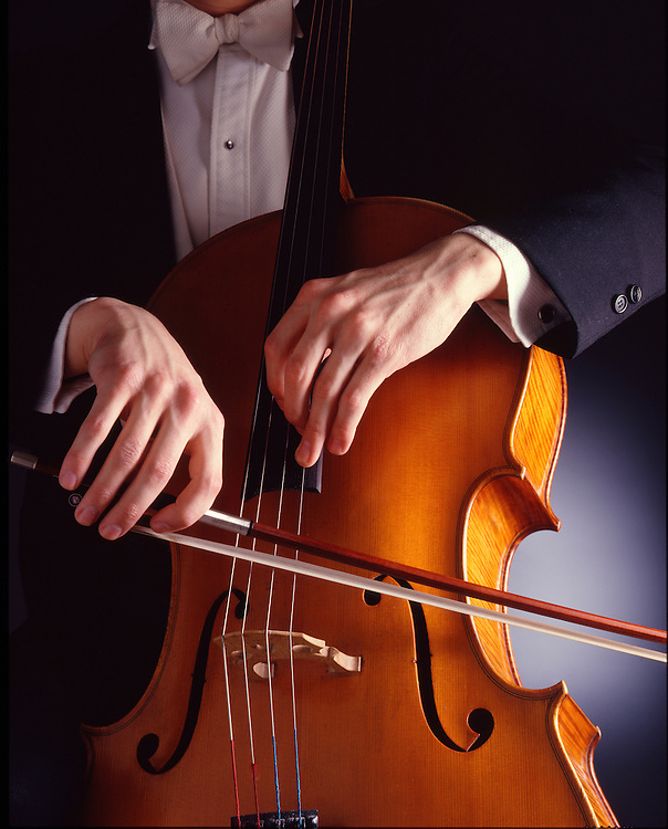 A close up of a cello player in tuxedo bowing his cello