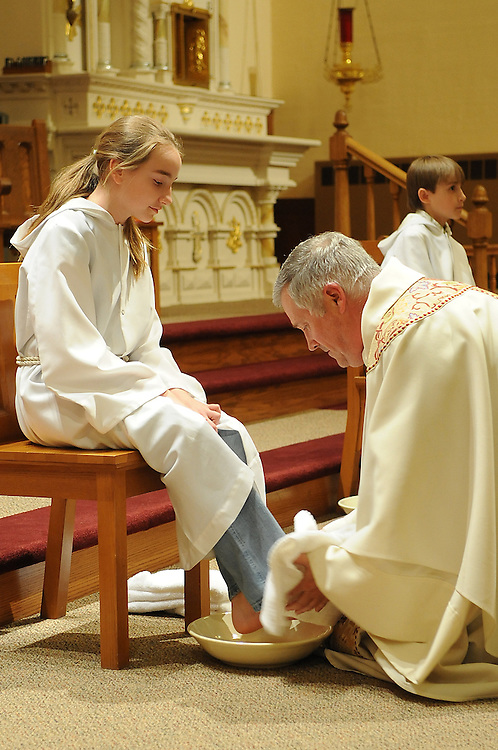 A priest washes the feet of a young server during Holy Thursday Mass in Algoma, Wis. (Sam Lucero photo)