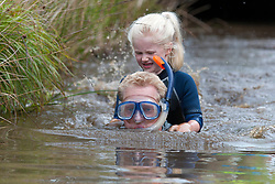 © Licensed to London News Pictures. 27/08/2017. Llanwrtyd Wells, Powys, Wales, UK. Tim Struth from Farnham, swims the bog with his daughter Phoebe aged 6. Phoebe has done the bog since age 21/2. The 32nd annual World Bog Snorkelling Championships, conceived over 30 years ago in a Welsh pub by landlord Gordon Green, are held at the Waen Rhydd Bog. Using unconventional swimming strokes, participants swim two lengths of a 55 metre trench cut through a peat bog wearing snorkel mask and flippers. Photo credit: Graham M. Lawrence/LNP
