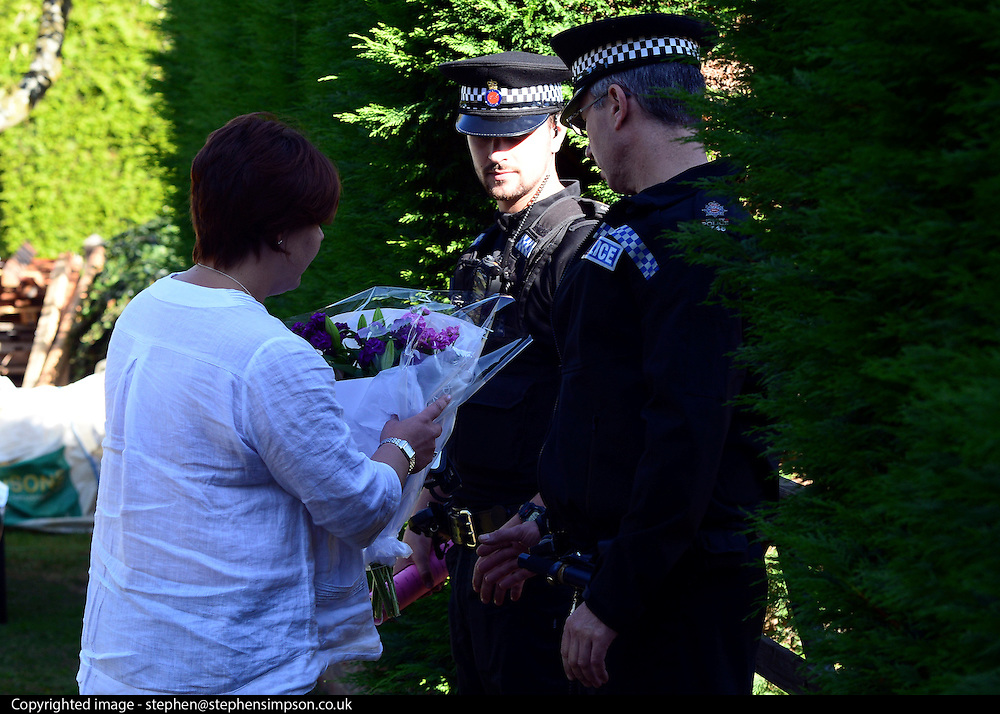 © Licensed to London News Pictures. 07/09/2012. Claygate, UK A woman hands over flowers to police officers. The family home of Saad al-Hilli in Claygate, near Esher. Three members ofof the family have been shot dead in the French Alps. Photo credit : Stephen Simpson/LNP