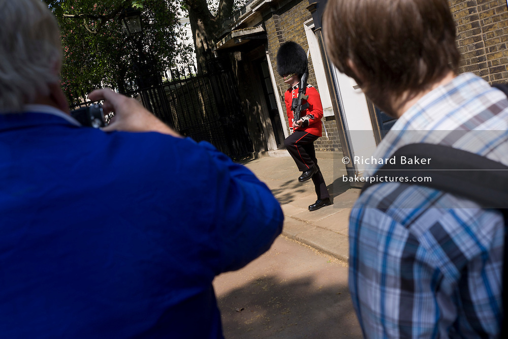 24 hours before the royal marriage of Prince William and Kate Middleton, a guardsman stands by his sentry box in front of Clarence House in St James Palace where the royal bride is staying. Two tourists stand admiring the soldier as he raises his leg to change his position. Taking place on Friday 30th April in front of millions of Britons and foreign tourists (many American), the crowds are already gathering to claim their ideal locations in the front rows along the procession route.