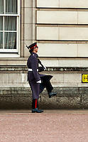 A palace guard marches in front of Buckingham Palace, London, England.