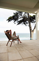 Woman looking at sea sitting on lounge chair by infinity pool