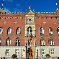 Town Hall or Rådhus in Odense, Denmark <br /> The location of Odense Town Hall has a very long history. The earliest settlement was formed here prior to 988 AD. Circa 1200, the current square became known as Flakhaven. In 1480, this became the site of the first town hall. It was replaced in 1885 by this red brick, Italian Gothic structure. The design was inspired by a town hall in Siena, Italy. The Rådhus still houses many of the city's municipal offices.