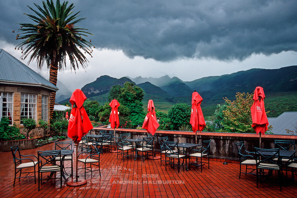 The restaurant terrace at Cathedral Peak Hotel is doused by a passing summer-afternoon thunderstorm.  The Drakensberg escarpment is one of the highest rainfall areas in South Africa, receiving more than 1,500mm per year.  About 85% of annual rainfall falls during the summer months (ie October to March), most of it directly as a result of orographic effects and the associated violent thunderstorms, like this one.  They are typically preceded by a mid-morning build-up of fluffy cumulus cloud and fully developed by midday.  Lightning and heavy rain is frequently accompanied by hail or sleet.   Just as quickly, they dissipate by mid-afternoon, often setting the stage for spectacular sunsets.  uKhahlamba Drakensberg Park, Kwa-Zulu-Natal, South Africa.  Nikon F100. Nikon AF Nikkor 24-85mm f/2.8-4D.  Kodak E100VS.