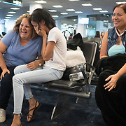 SEPTEMBER 23 - MIAMI, FLORIDA - <br /> Nicole Castro, 25, center  and her mother Beth Castro, 53, right, share a moment with Nicole's grandmother Zoraida Febo while waiting at an American Airlines gate at Miami International Airport after their 7:20AM flight to Puerto Rico was cancelled. The Castro family is trying to get to the island to visit family affected by the destructive path of Hurricane Maria.<br /> (Photo by Angel Valentin for NPR)