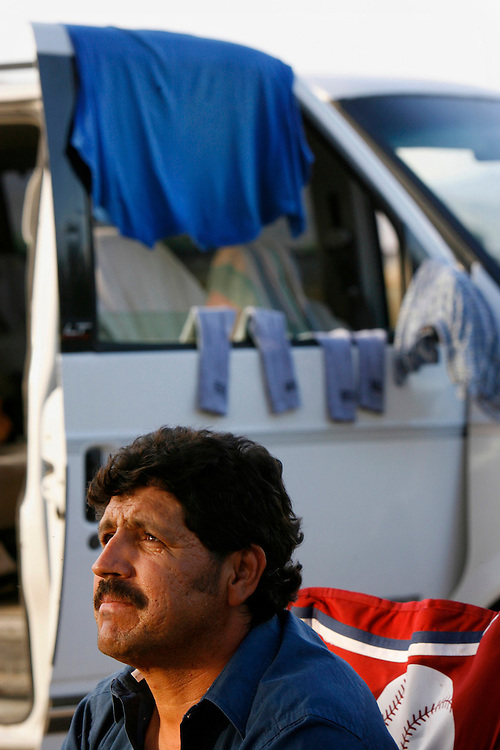 Mecca for Misery.Alfonso Jaurejui, 29, lives out of his van while working in Mecca, Ca. for the grape harvest. Jaurejui spends a few hours after work relaxing near a date grove to escape the crowd of workers in the parking lot at Leon's Meat Market. Jaurejui sleeps in the lot at night.