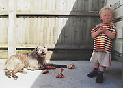 Toddler standing next to a dog eating meat, Winterbourne Travellers site, Bristol, UK, 1990's