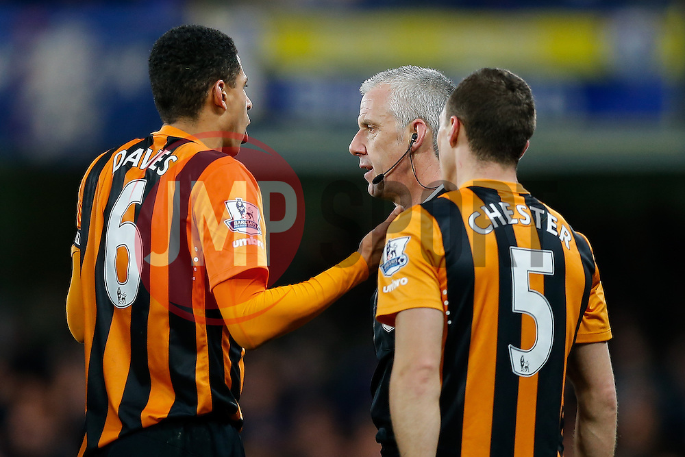James Chester and Curtis Davies of Hull City argue with referee Chris Foy after he shows a redcard to Tom Huddlestone - Photo mandatory by-line: Rogan Thomson/JMP - 07966 386802 - 13/12/2014 - SPORT - FOOTBALL - London, England - Stamford Bridge - Chelsea v Hull City - Barclays Premier League.