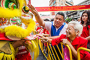 """10 FEBRUARY 2013 - BANGKOK, THAILAND: People pet and place money into the """"mouth"""" of a Lion during a Lion Dance on Chinese New Year along Yaowarat Road in the Chinatown section of Bangkok. Bangkok has a large Chinese emigrant population, most of whom settled in Thailand in the 18th and 19th centuries. Chinese, or Lunar, New Year is celebrated with fireworks and parades in Chinese communities throughout Thailand. The coming year will be the """"Year of the Snake"""" in the Chinese zodiac.    PHOTO BY JACK KURTZ"""