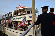 Freeport, New York, USA. September 10, 2014. After a dockside remembrance ceremony in honor of victims of the terrorist attacks of September 11 2001, passengers walk up the gangplank to board the boat Miss Freeport V, which sailed from the Woodcleft Canal on Freeport's Nautical Mile on Long Island, on the eve of the 13th Anniversary of the 9/11 attacks. Further ceremonies were held on the boat.