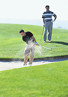 A young man hits a golf shot out of a sand trap while another golfer watches<br />