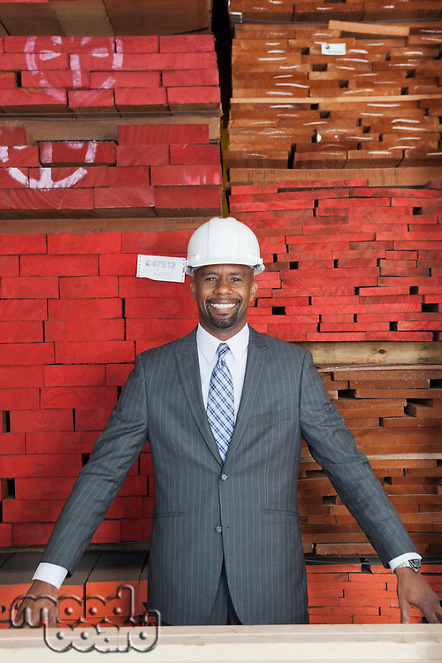 Portrait of happy African American male contractor with stacked wooden planks in background