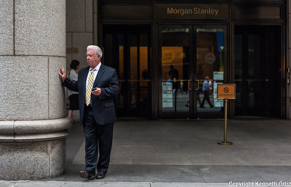 A man takes a break and stands in front of the Morgan Stanley building on 5th Avenue in New York City.